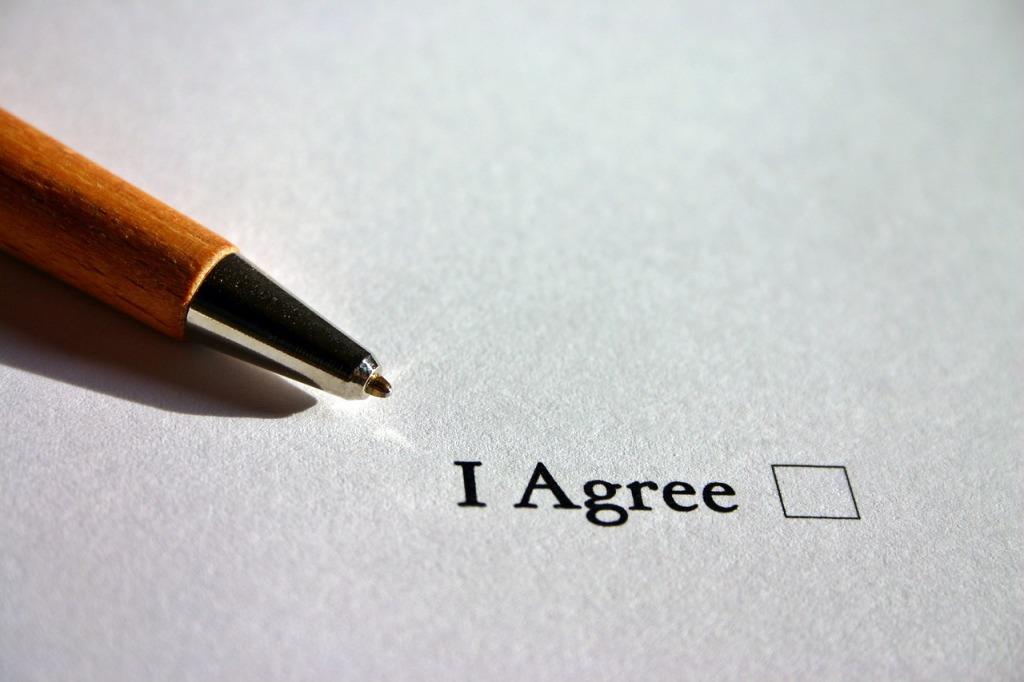 """Caneta ao lado da frase """"I agree"""", junto a um checkbox."""