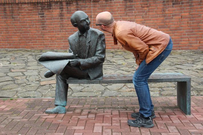 Homem tenta se comunicar, mas o ouvinte é uma estátua, demonstrando que não há comunicação efetiva.